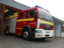 a fire engine leaving a station in response to an emergency call