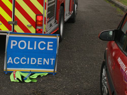A police sign in front of a fire engine at the scene of a road traffic collisions
