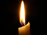 Candle burning in a dark room